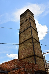 A tall, well maintained chimney reaches high into the sky.