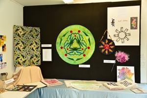 "Debora's circular wall hanging was based on the plant world. To the right is Grace's ""Feeling Groovy""  hanging and Fibonacci principles based mask."