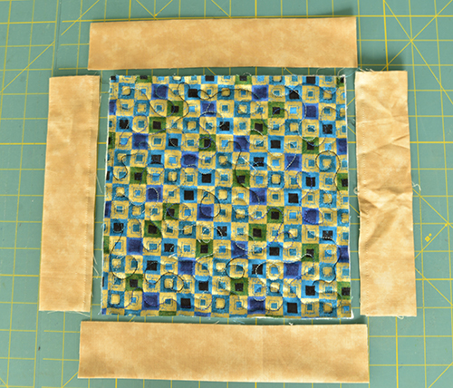 "Step 5: Cut two strips exactly the length of left and right of quilt. Cut two more strips approximately 1"" longer on either side of the edge."