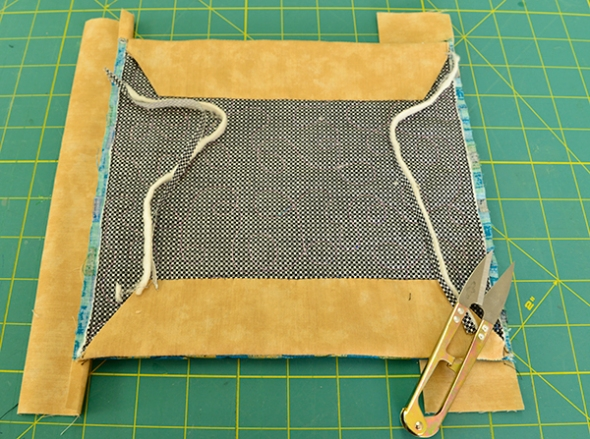 Step 17: Turn over the quilt and trim away the batting and backing layers (as in step 8).