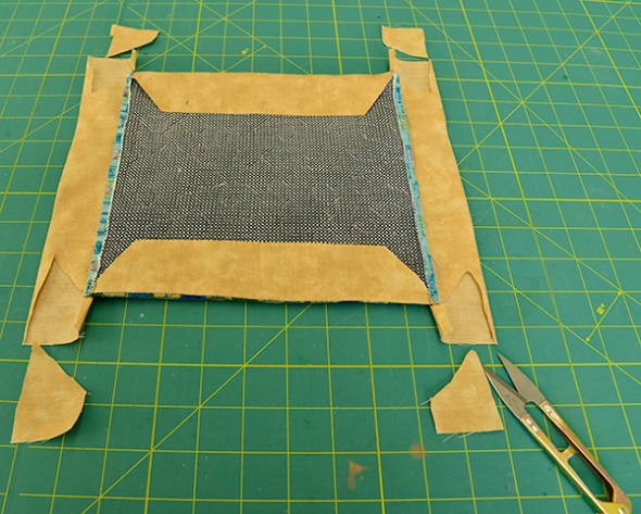 Step 18: Trim excess fabrics as demonstrated here. This will further reduce bulk when finishing the corners of the quilt.