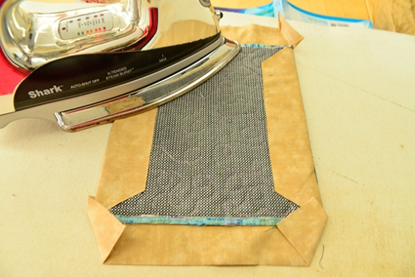 Step 19: Take the quilt to the ironing board. Carefully press the strips to the back (as in  step 12).