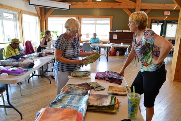 Leona and Paula are looking over the fabrics created during the week.