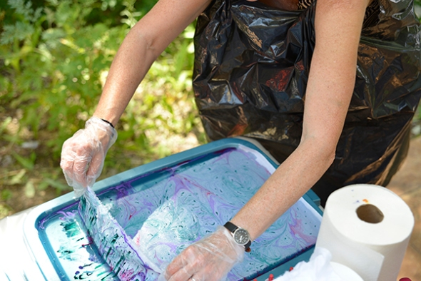 Placing the prepared fabric over the marbling medium and paint.
