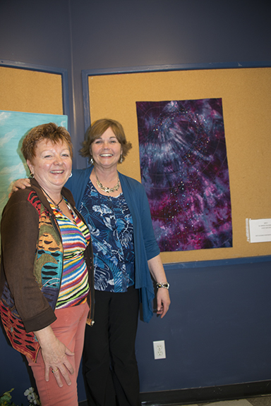 Shirley Mathieson from Moose Jaw (right) was the trunk show presenter Friday night. Bonnie (left) was her hostess and helper while hanging her hand-dyed and beaded piece.