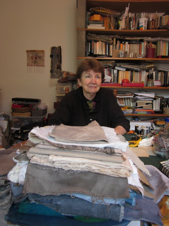Joanne Young in her studio, immersed in fabric and other support materials.